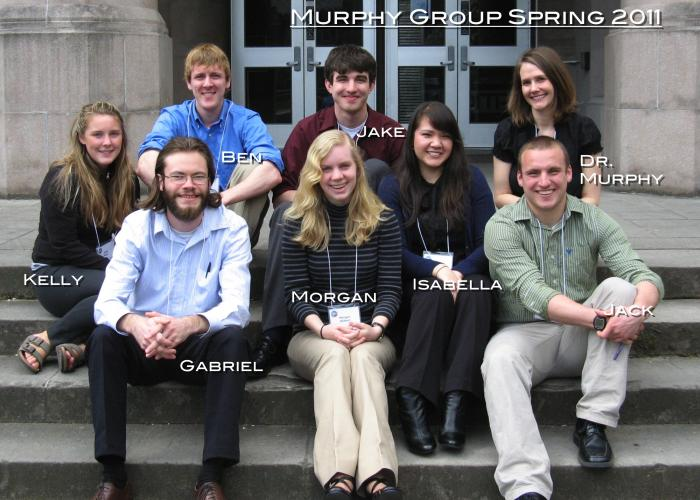 "A group of students and Amanda Murphy sit on concrete steps, smiling at the camera. The photo is labeled ""Murphy Group Spring 2011"""