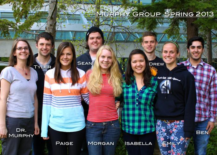 "A group of students and Amanda Murphy stand in front of a building, smiling at the camera. The photo is labeled ""Murphy Group Spring 2013"""