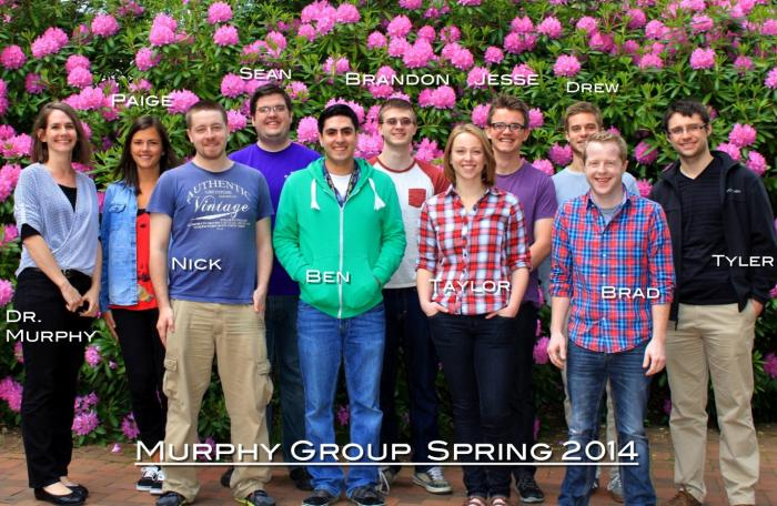 "A group of students and Amanda Murphy stand in front of floral plants, smiling at the camera. The picture is labeled ""Murphy Group Spring 2014"""