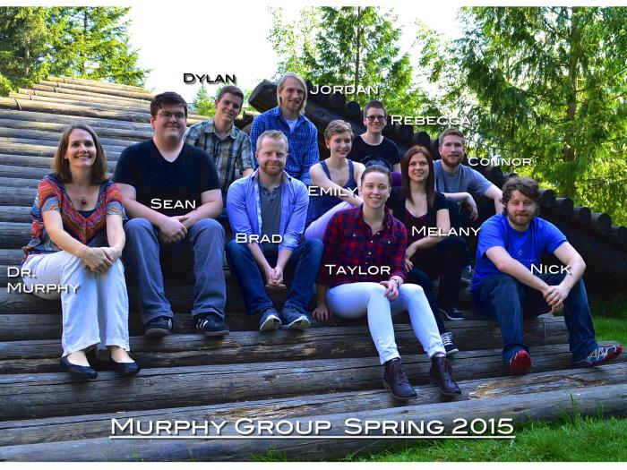 "A group of students and Amanda Murphy sit on a wooden sculpture, smiling at the camera. The photo is labeled ""Murphy Group Spring 2015"""