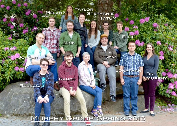 "A group of students sit on boulders in front of floral plants, smiling at the camera. The photo is labeled ""Murphy Group Spring 2016"""