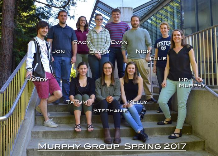 "A group of students and Amanda Murphy pose on concrete steps. The photo is labeled ""Murphy Group Spring 2017"""
