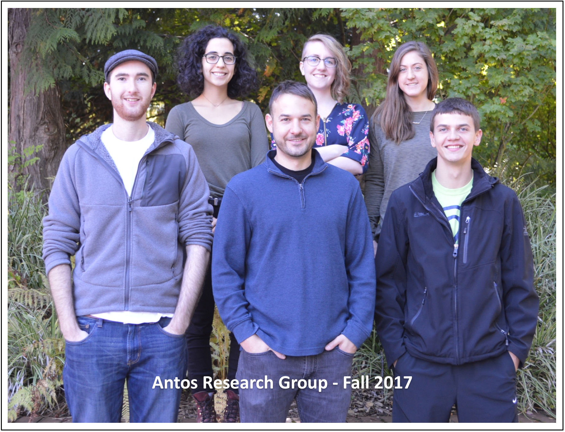 "A group of six students pose in front of trees. The picture is labeled ""Antos Research Group Fall 2017"""