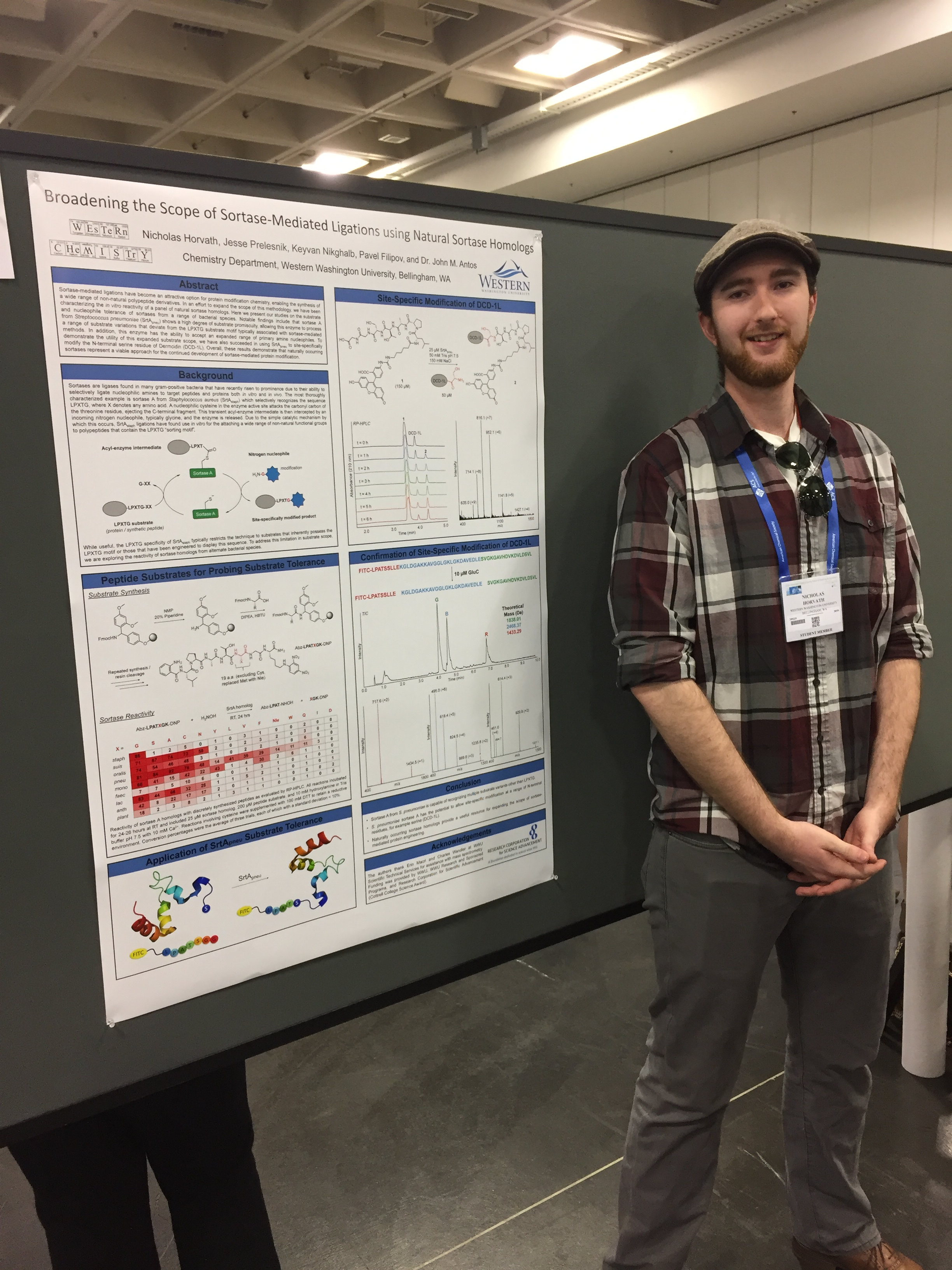 Nicholas Horvath smiling next to his research poster