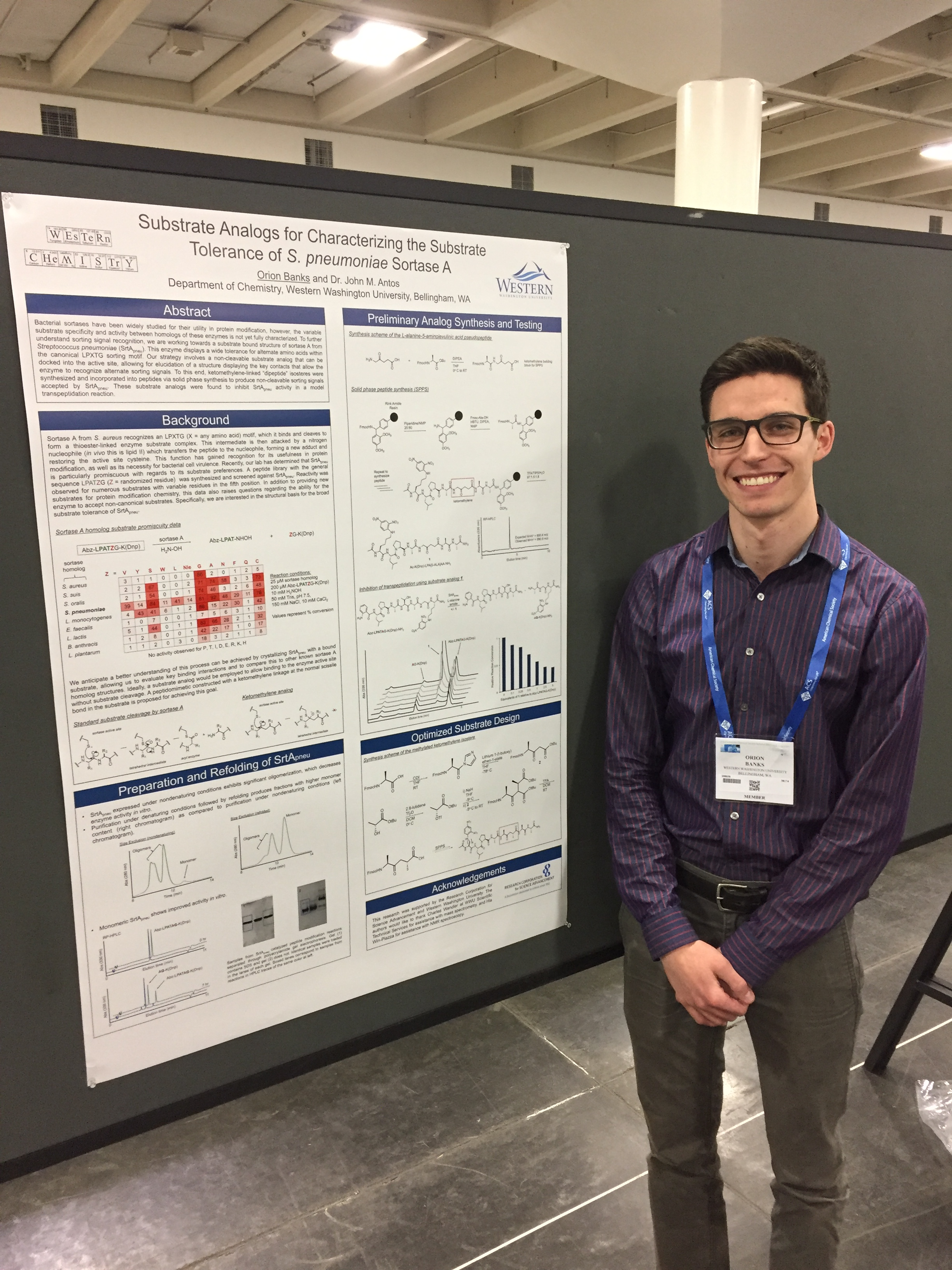 Orion Banks smiling next to his research poster