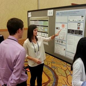 Student presenting poster while others watch