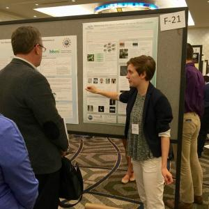 Student presenting poster to group of people at conference