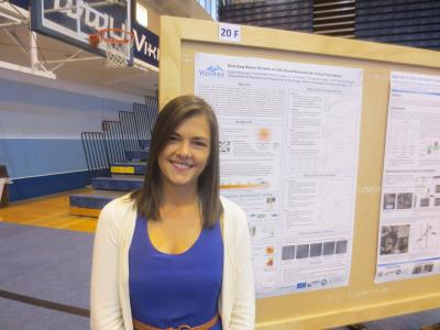 Student stands in front of research poster