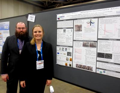 Two students standing in front of their poster at conference