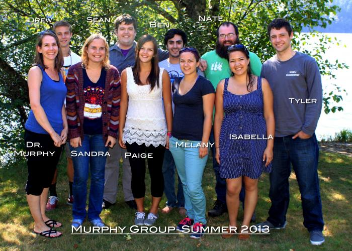 "A group of students and Amanda Murphy stand in front of a tree, smiling at the camera. The photo is labeled ""Murphy Group Summer 2013"""